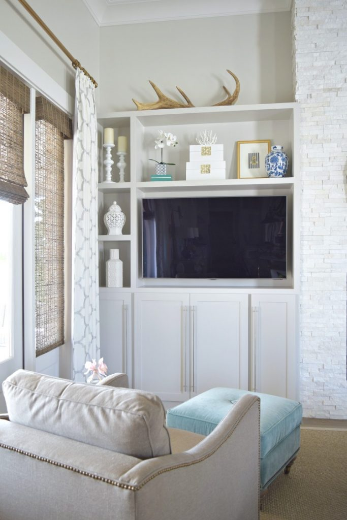 shelf-styling-accessories-living-room-teal-tufted-ottoman-white-ginger-jars-gray-cabinets