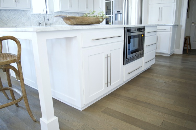 white-kitchen-island-carrara-marble-counter-tops-herringbone-backsplash-modern-shaker-cabinets