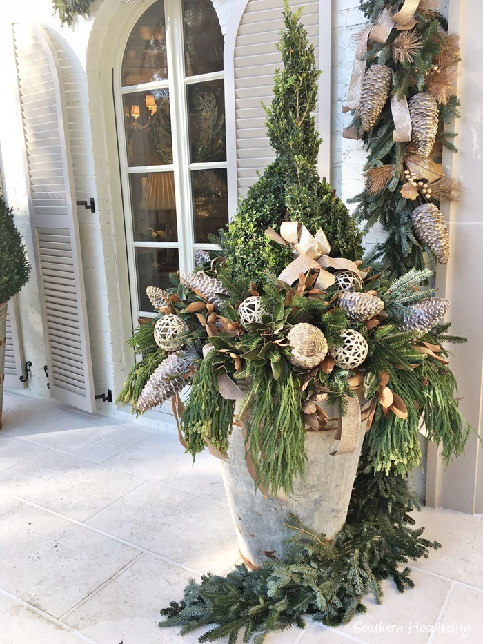 Zinc planter with boxwood and fresh evergreens decorated for Christmas on French Country home porch
