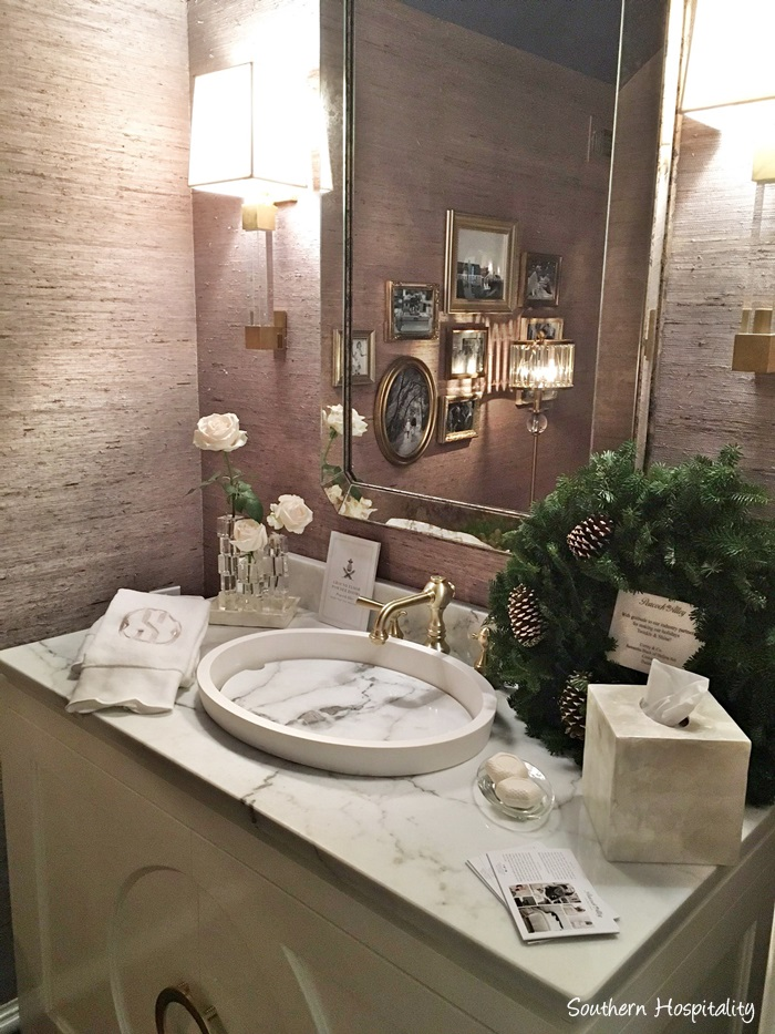 Powder room in Atlanta showhouse 2016 with grasscloth wall covering, marble sink, and gilded frames