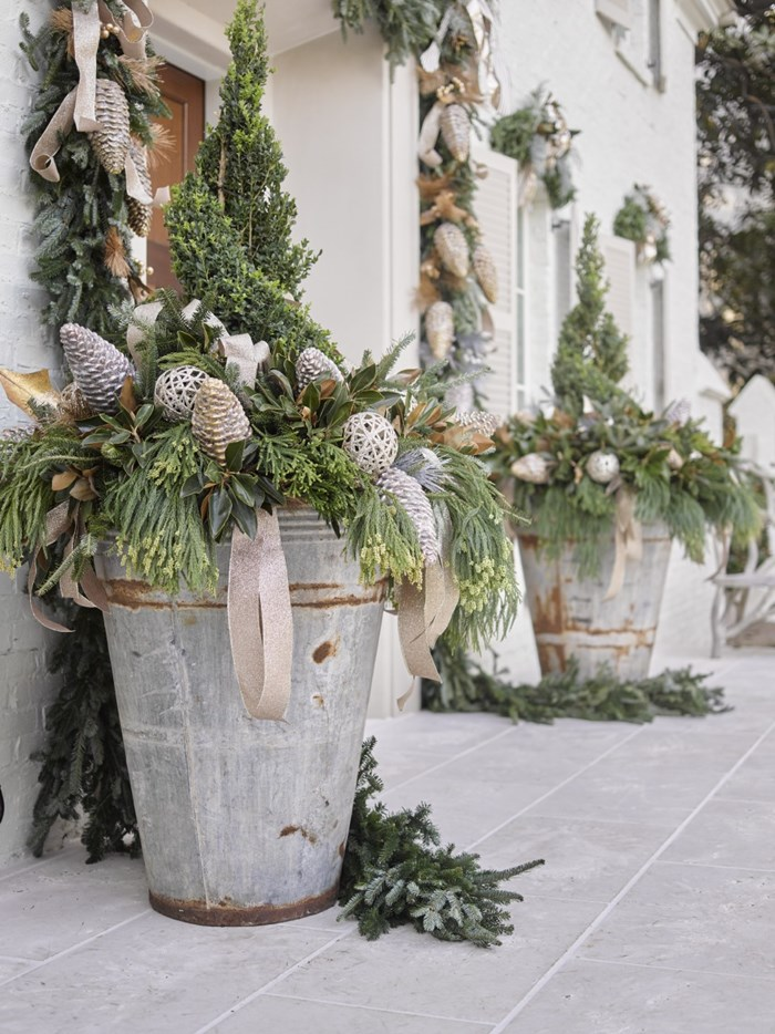 Enormous rustic zinc olive planters filled with Christmas greenery on French Country showhouse porch