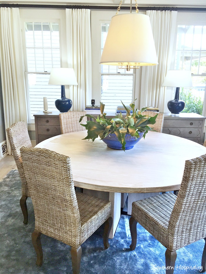 Dining Area With Wicker Chairs And A Pretty Light Wood Round Table That Rug Is So Soft Cozyand Blue