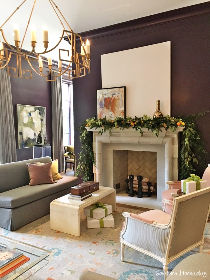 Gorgeous garland on stone fireplace in room painted eggplant in Atlanta holiday showhouse 2017