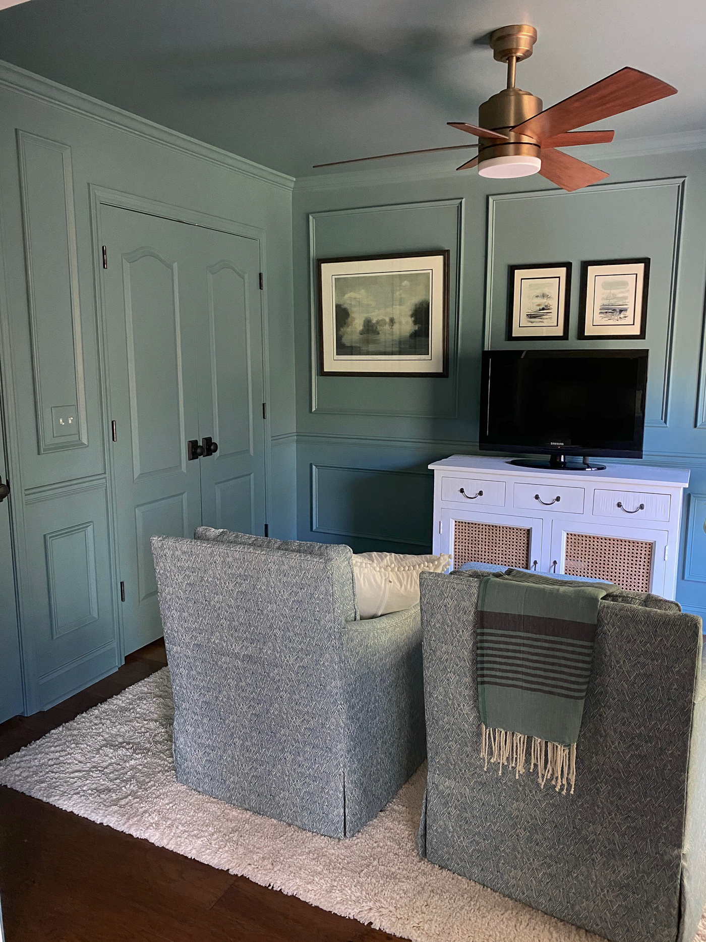 Moody blue sitting room with picture frame molding painted all one color